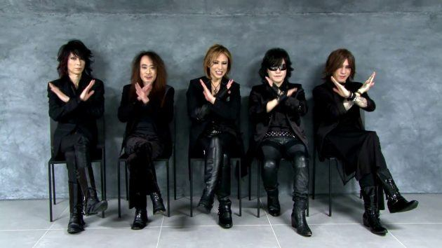 椅子に座ってXポーズをしているメンバー5人が揃うX JAPANの画像
